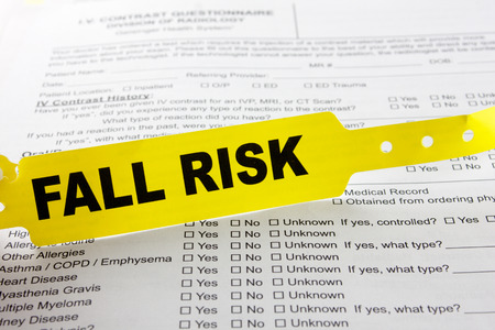 A yellow fall risk patient bracelet on top of a hospital questionnaire paperwork
