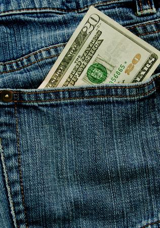 A twenty dollar bill sticking out the back pocket of denim blue jeans Stock Photo