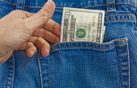 A person pulling a twenty dollar bill out of a denim blue jean back pocket