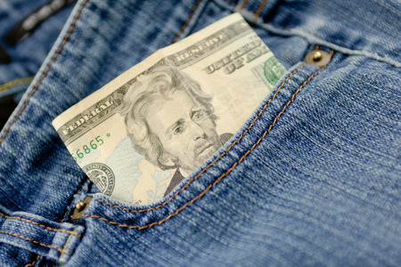 A twenty dollar bill sticking out the front pocket of denim blue jeans