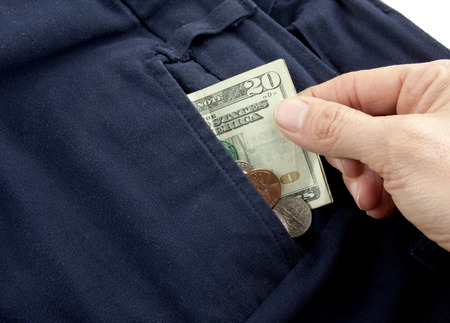 A twenty dollar bill sticking out the front pocket of dress jeans with coins