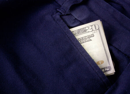 A twenty dollar bill sticking out the front pocket of dress jeans photo