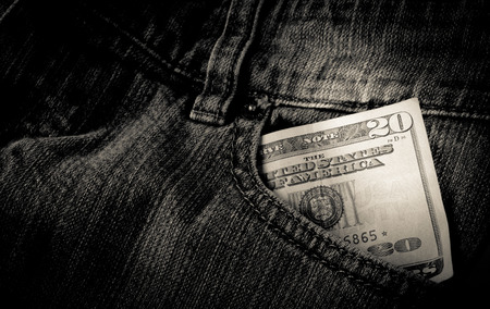Cash in a front pocket of a pair of black jeans Stock Photo