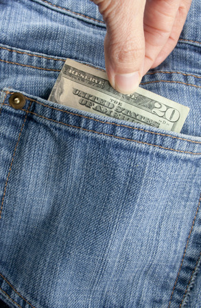 A person pulling a twenty dollar bill out of a denim blue jean back pocket photo