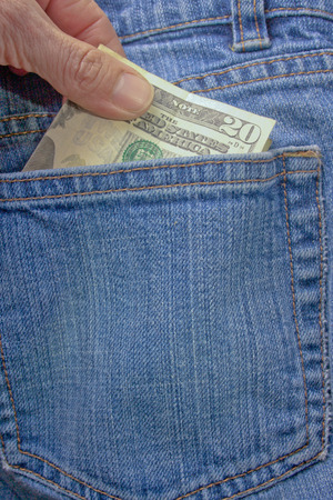 A person pulling a twenty dollar bill out of a denim blue jean back pocket