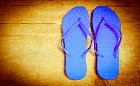 Blue flip-flops on a wooden textured