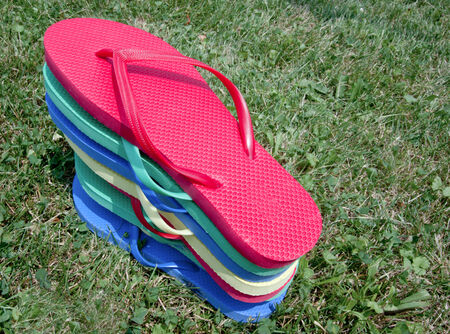 Flip-flops stacked in a yard in the grass Stock Photo