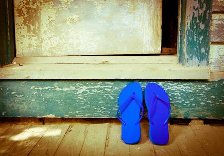 Blue flip-flops leaning against a house