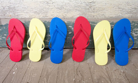 Multi colored flip-flops leaning against a house Stock Photo