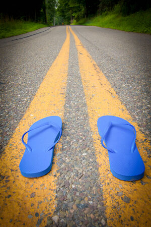 Blue flip-flops in the center of the road Stock Photo