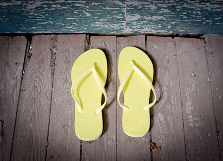 A pair of yellow flip-flops sitting on the porch Stock Photo