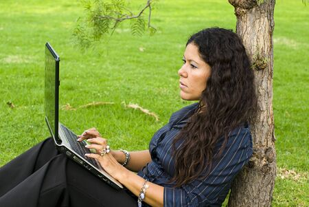 profesional: woman with laptop sitting in grass Stock Photo