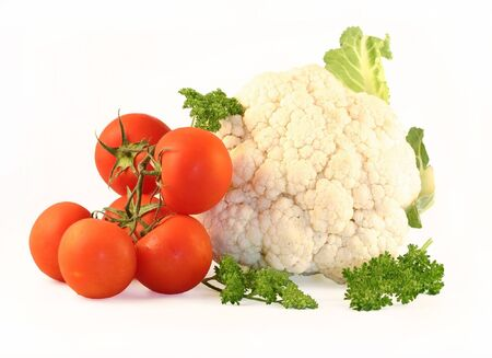 The cauliflower and tomatoes are photographed on a white background close up. Beside the parsley lays.