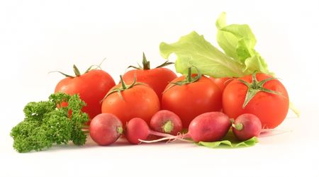 Some tomato lay in an environment of a garden radish, salad and a parsley on a white background.