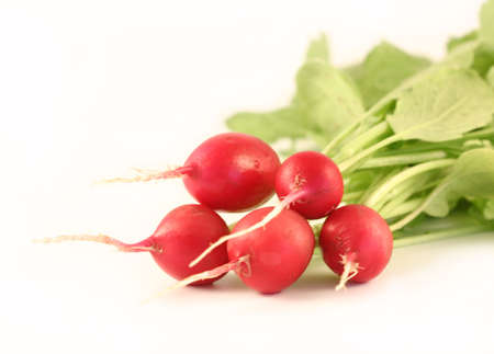 The bunch of a garden radish lays on a white background. It is photographed close up.