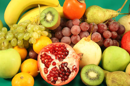 Different fruit on a green background.