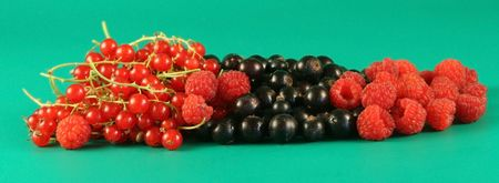 wooden lid: Red currants, a black currant and a raspberry on a green background.  Stock Photo