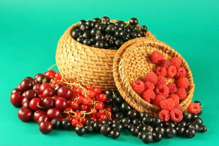 Berries of a red currant, a black currant, a raspberry and a cherry in a basket. Stock Photo