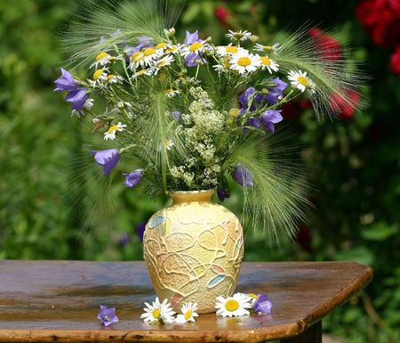 The bouquet of field flowers stands on a table in a garden.