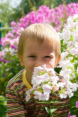 Happy boy in the garden among the flowers