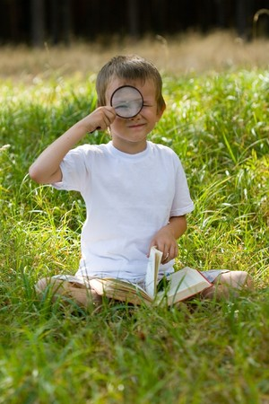 Happy boy with a magnifying glass and a book outdoors on a summer day