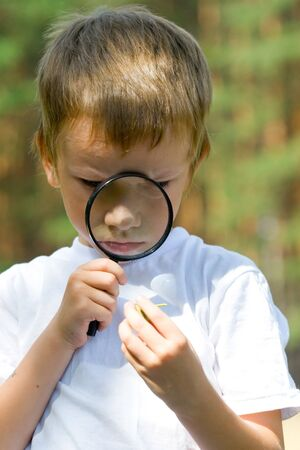 Happy boy with a magnifying glass  outdoors on a summer day