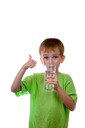 boy drinks water from a glass on a white background photo