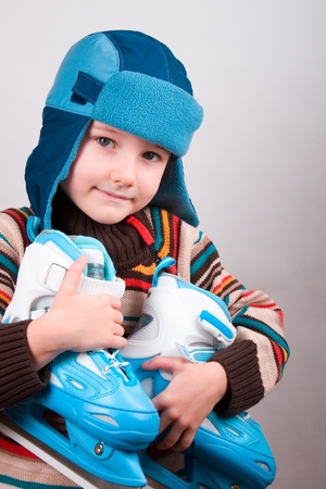 Boy in  hat  and  jacket  keeps  his  skates Stock Photo