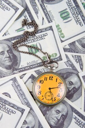 Pocket watch on a stack of dollars, reflecting time and money  photo