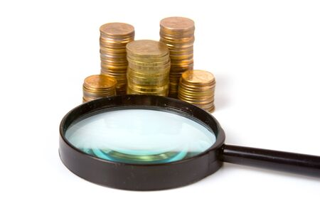Piles of gold coins and magnifying glass on a white background Stock Photo - 9081606