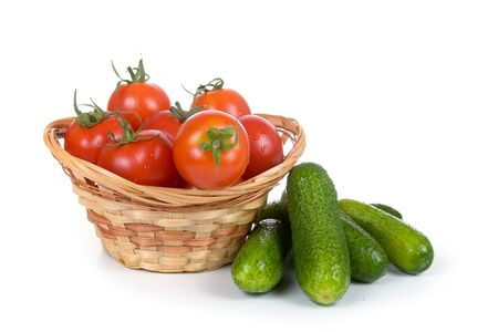 Ripe vegetables in a wicker basket isolated on a white background