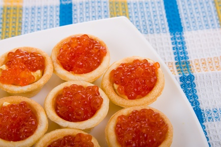 Tartlets with red caviar on a blue tablecloth