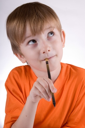 Cheerful boy with a pencil looks toward on a white background Stock Photo
