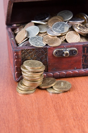 Open chest with coins on a wooden surface close-up photo