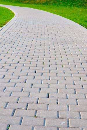 Garden stone path with grass growing around stones photo
