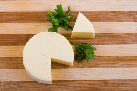 Cut round cheese on a wooden board Stock Photo - 10952267