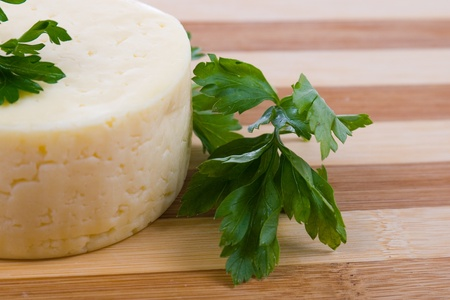 Round cheese on a wooden board Stock Photo - 11009277
