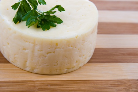 Round cheese on a wooden board Stock Photo - 11264953