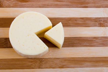 Cut round cheese on a wooden board Stock Photo - 11264963