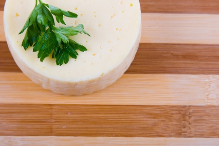 Round cheese on a wooden board Stock Photo - 11265144