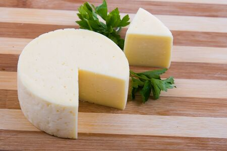 Round cheese on a wooden board Stock Photo - 11265108