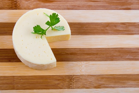 Round cheese on a wooden board Stock Photo - 11265158