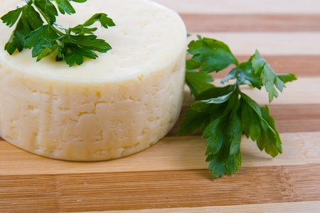 Round cheese on a wooden board Stock Photo - 11433166
