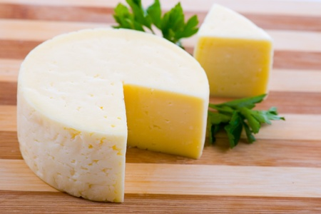 Round cheese on a wooden board Stock Photo - 11704533