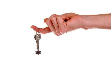 Hand holding keys. Keys to new house hanging on the finger o a white background photo