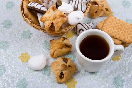 White cup of tea and  different biscuits on the table  photo