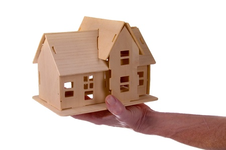 Hand holding a wooden house isolated on white background photo