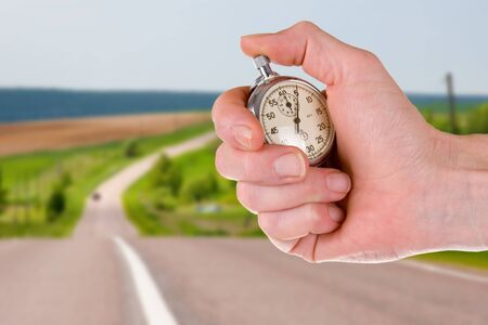 Hand with a stopwatch on the background of a summer road Stock Photo