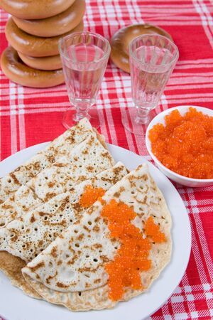 Pancakes with red caviar and vodka.The celebration of Maslenitsa - Russian religious and folk holiday. photo