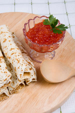 maslenitsa: Pancakes with red caviar on a plate. The celebration of Maslenitsa - Russian religious and folk holiday. Stock Photo